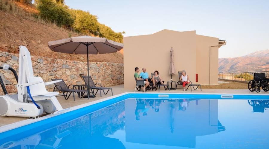 Sdraio e tavolini nei pressi della piscina