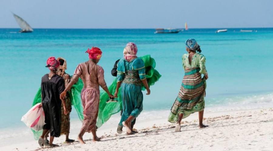 lugareños que pasean en la playa de la isla de la mafia