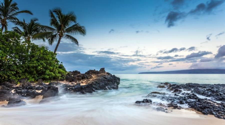 Waves crashing on the beach of Secret cove at dawn on Maui