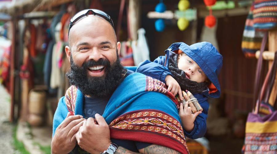 Papà con figlio in un colorato mercato peruviano