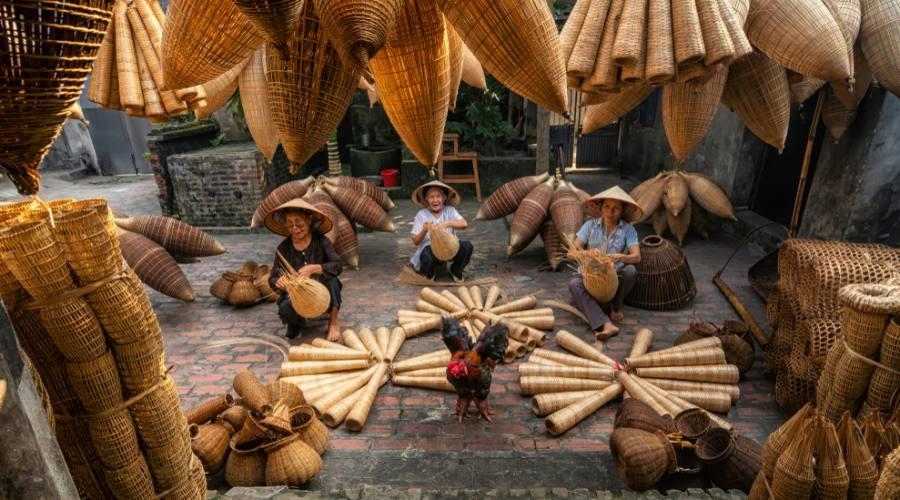 Donne vietnamite che intrecciano cesti