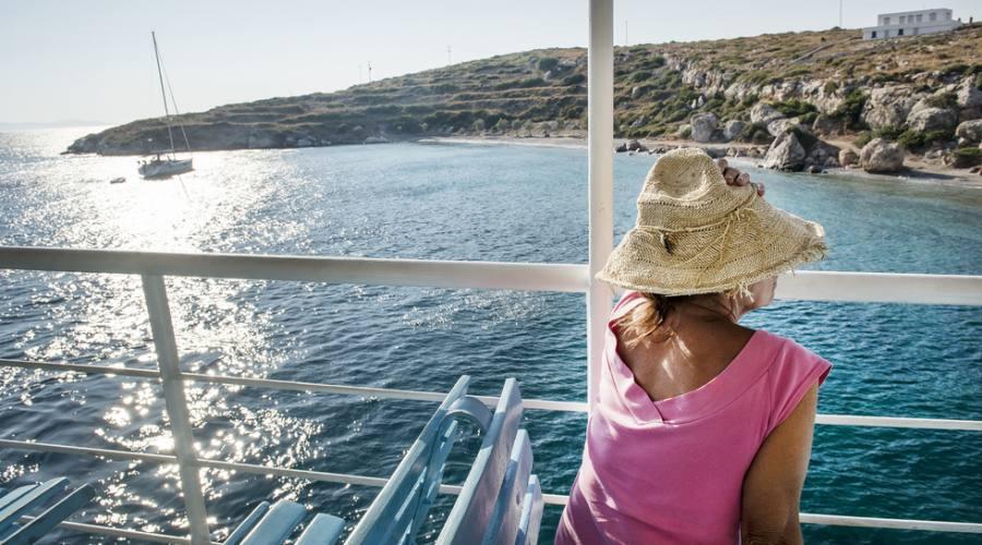 Una donna si siede a bordo di un traghetto mentre passa accanto a un'isola greca nel Mar Egeo